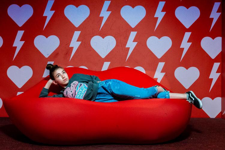 Full length of cute boy lying on red carpet