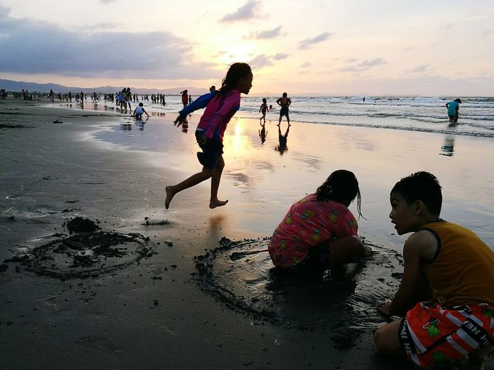 Children playing on beach against sky during sunset