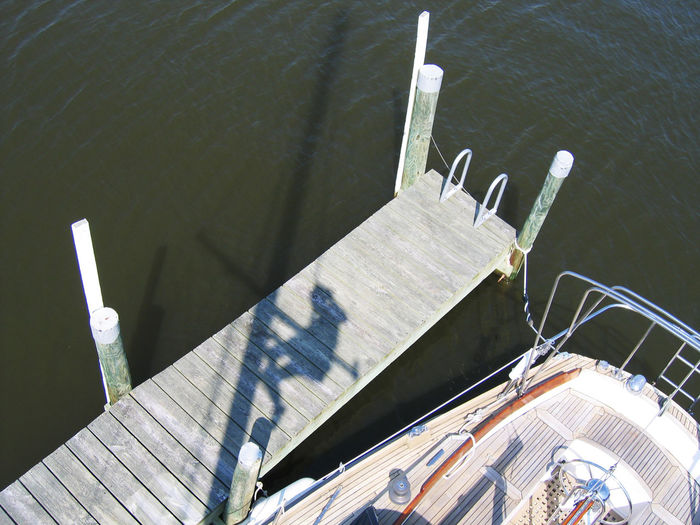 At The Marina Boat Worker Flying High One Mast Sailboat Sailboat Mast Shadow Up The Mast