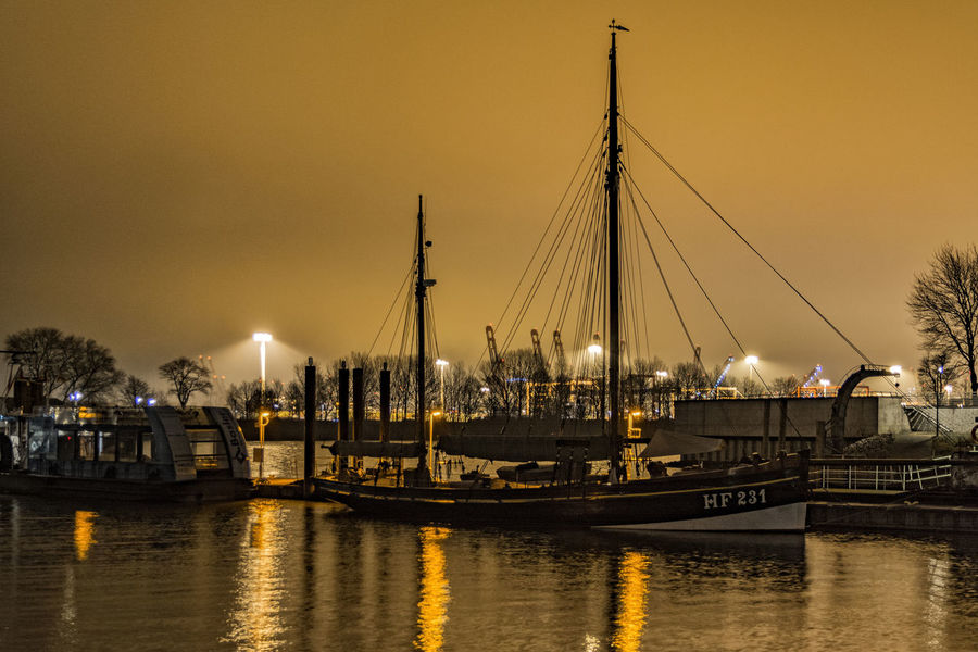 Sail boat Artificial Lights Bridge - Man Made Structure Built Structure Cultures Finkenwerder Hamburg Hamburg Harbour Harbor Illuminated Nautical Vessel Night Night Photography No People North Germany Orange Outdoors River Sky Transportation Travel Destinations Water Water Reflections