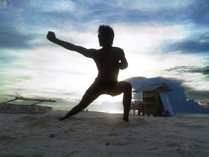 Full length of silhouette young man exercising at beach against cloudy sky during sunset