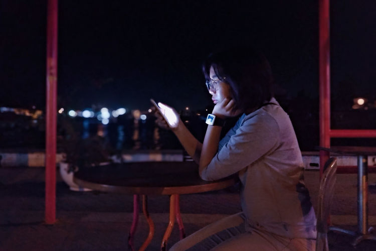 Side view of woman using mobile phone at night