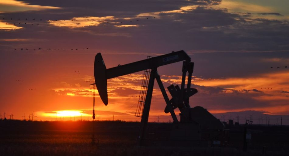 Silhouette Oil Pump Against Cloudy Sky During Sunset