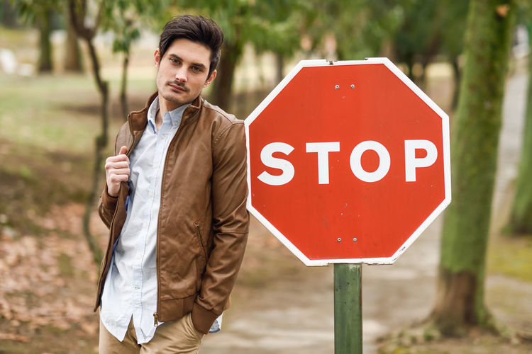 Portrait of young man standing by stop sign