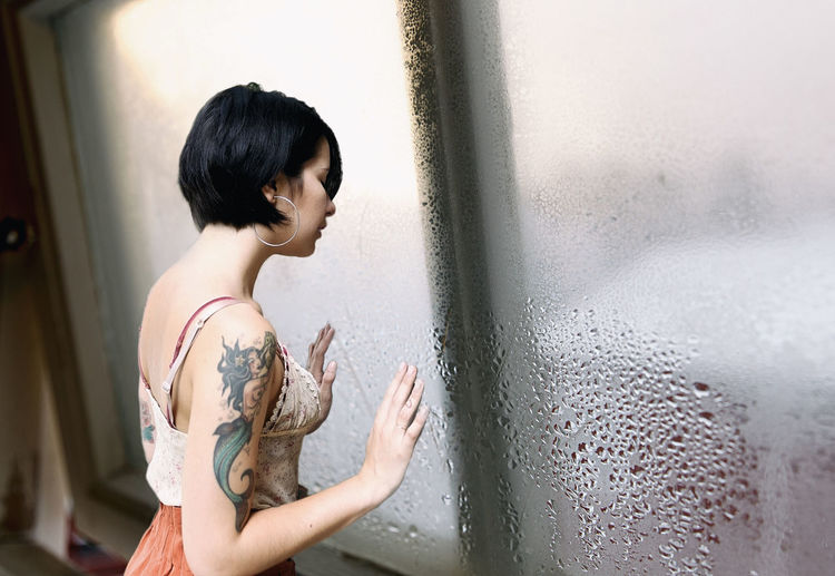 Side view of woman standing by wet window