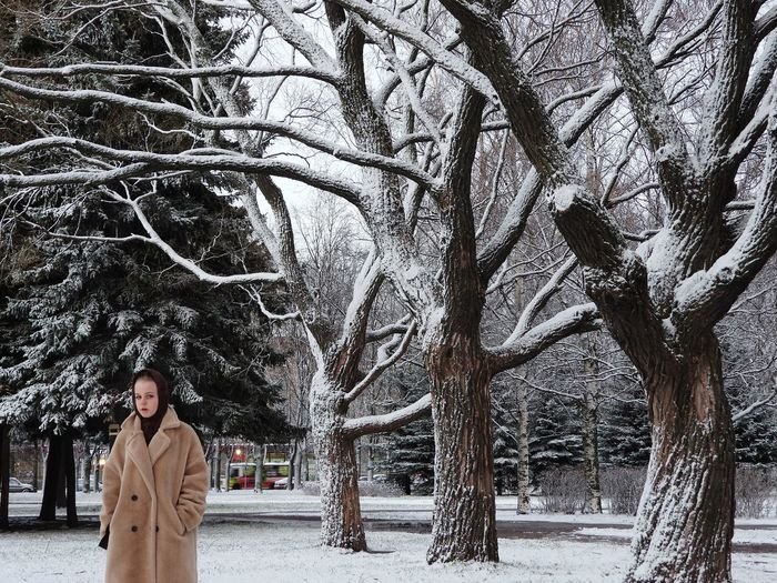 Woman standing by tree during winter