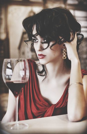 Beautiful Woman Sitting By Red Wine In Restaurant