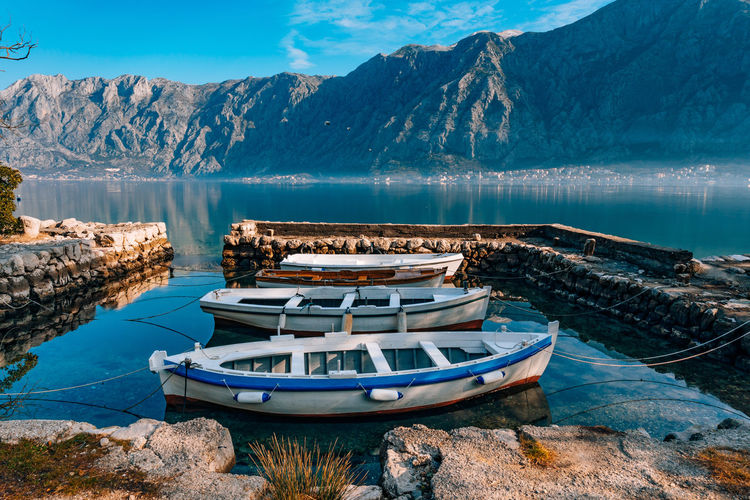 Ship moored on lake against mountains
