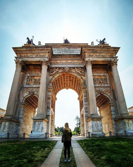 Rear view of woman standing at triumphal arch against sky