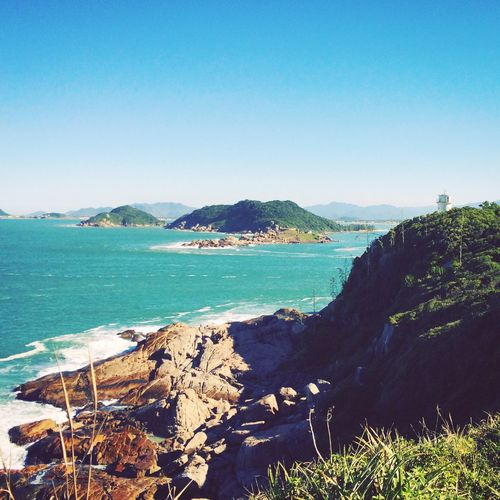 Naufragados beach trail. Florianópolis - Brazil. Clear Sky Water Nature Scenics Sea Beauty In Nature Tranquil Scene Outdoors Mountain Blue Day Tranquility No People Sunlight Sky light house Coastline Travel Waterfront Idyllic Travel Destinations Remote Brazil Vacations Beach View