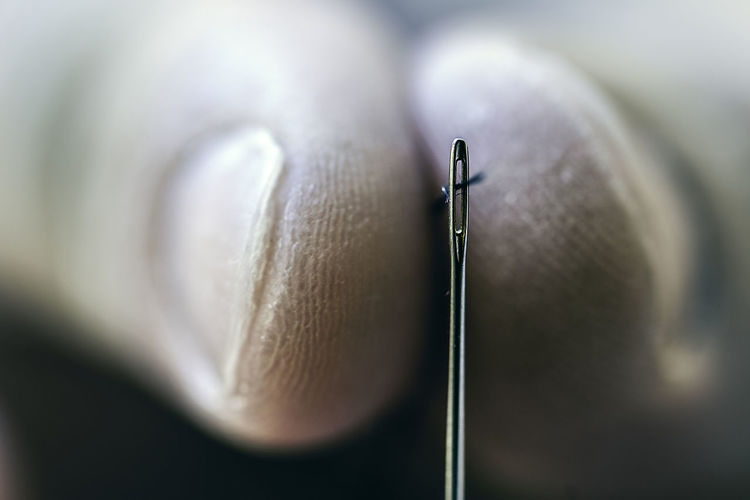 Extreme close-up of hand putting thread in needle