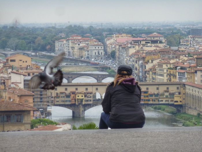 Woman watching cityscape of florence Cityscape Building Exterior Architecture City Rear View Built Structure Outdoors One Person Animal Themes People Adult River EyeEm Gallery Ladyphotograferofthemonth Florence Italy Ponte Vecchio Looking Down View From Placa Michelangelo Dove In Flight Women Around The World