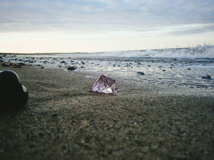 Diamond on beach against cloudy sky