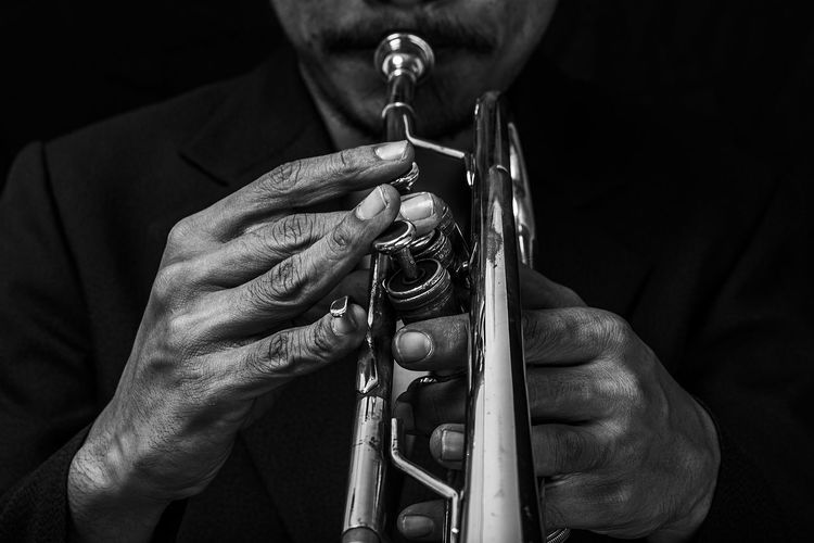 Midsection of man playing trumpet