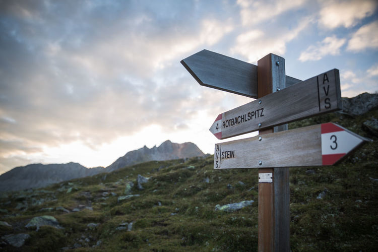 Road Sign On Mountain Against Cloudy Sky