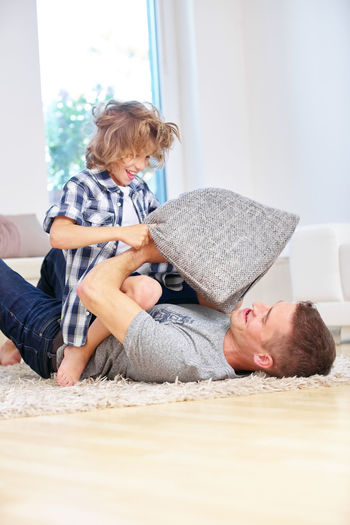Playful son fighting with father lying on rug at home