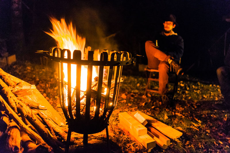 Young man sitting at campsite during night