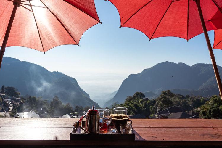 Umbrellas on table against mountain range