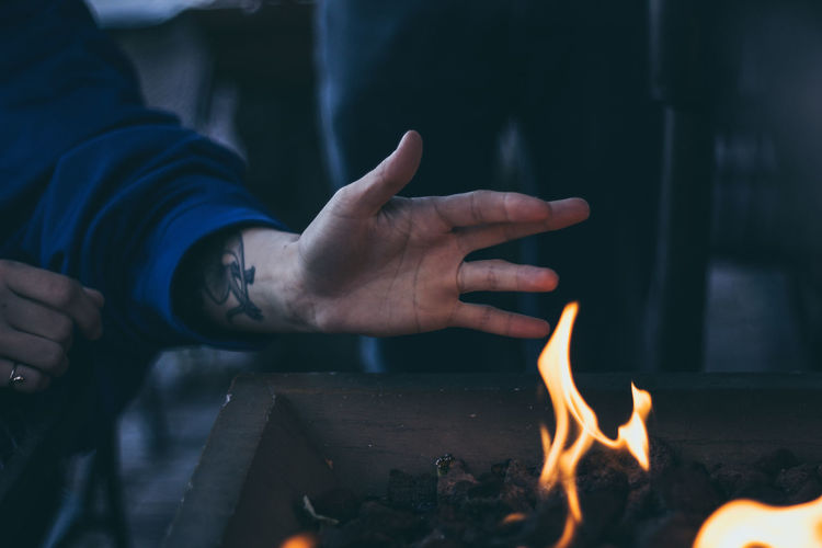Close-up of human hand by fire