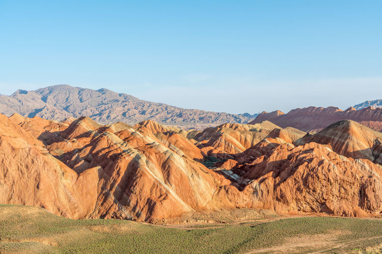 Colourful rock and distance mountains at the Zhangye Danxia Landform Arid Climate Arid Landscape Blue China Clear Sky Colorful Rocks Desert Gansu Gansu Province High Resolution Landscape Mountain Mountain Range Nature No People Orange Color Physical Geography Red Remote Sky Tranquility Travel Travel Destinations Zhangye  Zhangyedanxialandform