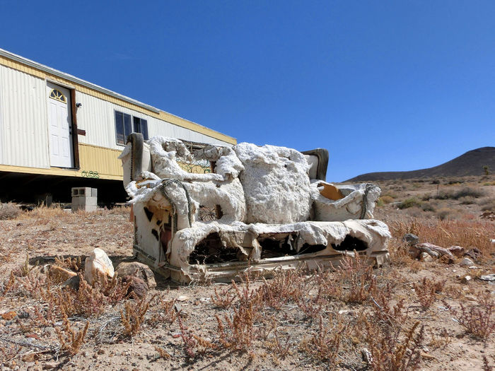 Abandoned Sofa By Travel Trailer On Field Against Clear Blue Sky