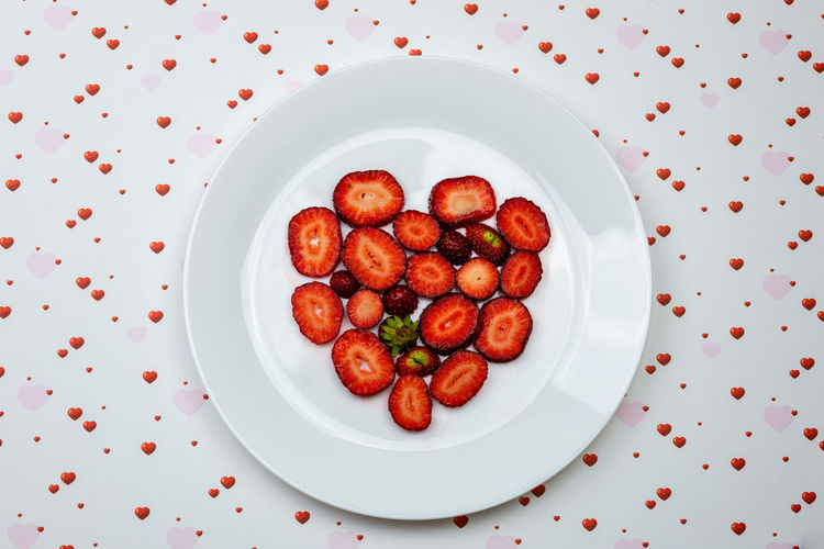 Creative Valentine Day romantic concept composition flat lay top view with heart strawberries on a white plate isolated on a heart background. Food And Drink Food Freshness Red Indoors  Still Life No People Strawberry Strawberries Fruit Fruits Fresh Healthy Eating Natural Raw Vitamin Raw Food Tasty Breakfast Ripe Juicy Sweet Berry Delicious Nutrition Background Rustic Dessert Freshness Eating Organic Close-up Diet Ingredient Vegan Snack Apperitive Pattern Flat Flat Lay Heart Shape Valentine's Day  Valentine Romantic Concept Vegetable Directly Above Plate Table High Angle View Ready-to-eat Wellbeing White Color
