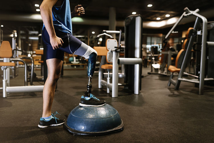Low section of man with prosthetic leg exercising in gym