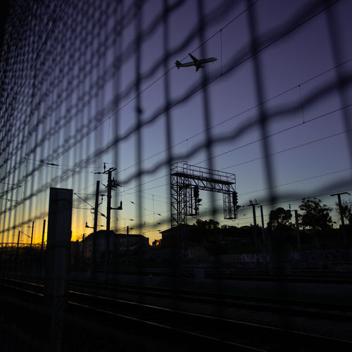 Silhouette railroad station against sky at dusk