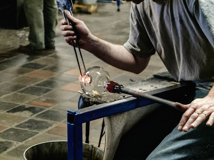 Midsection of male worker making glass in factory