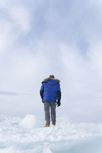 Rear view of man walking on snow against sky