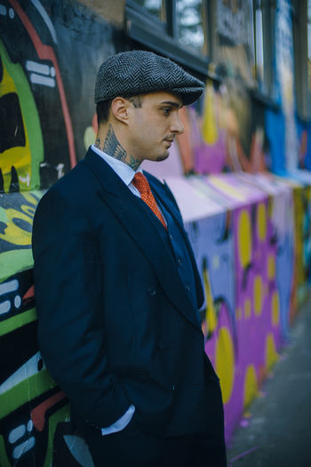 Thoughtful young male model standing against graffiti wall