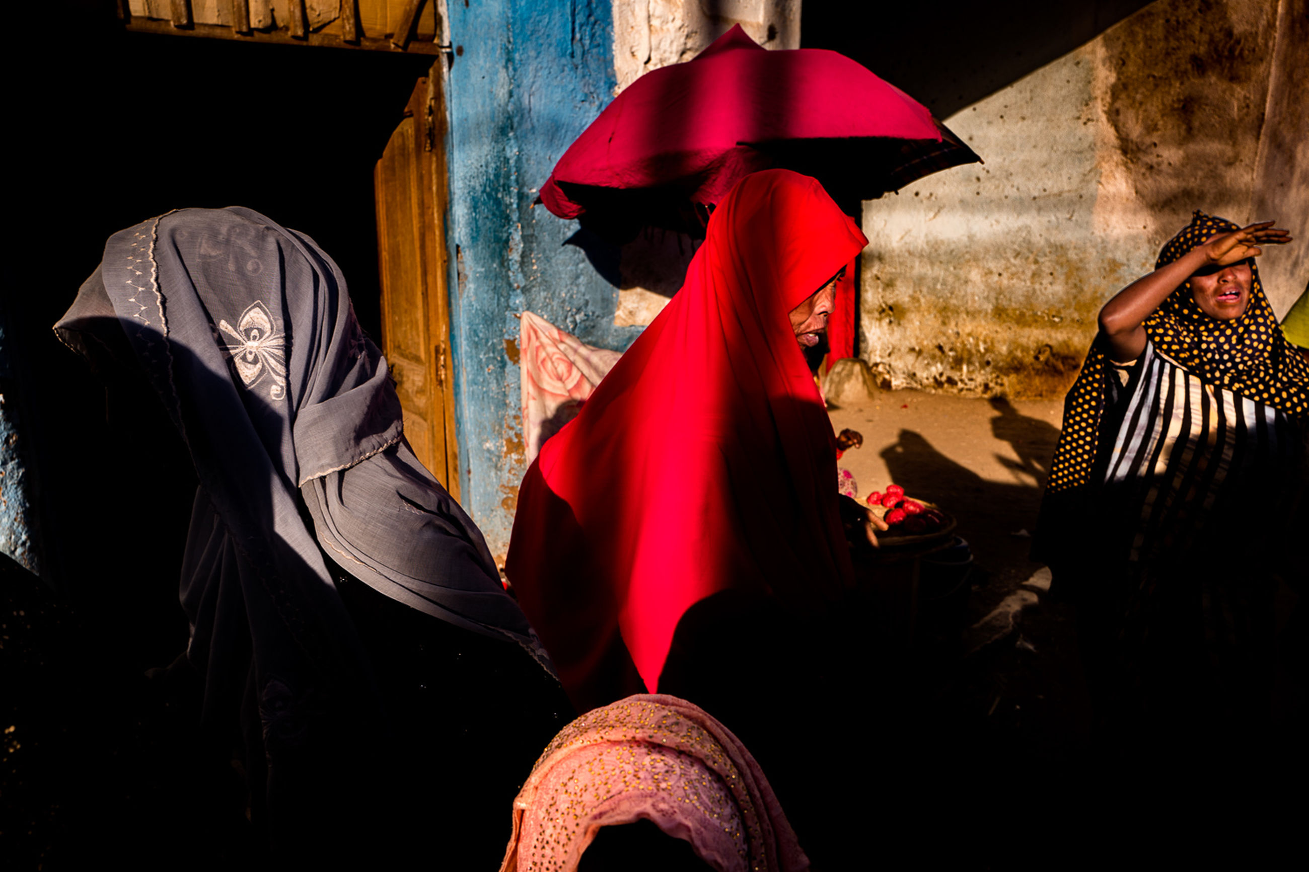 real people, lifestyles, people, umbrella, clothing, leisure activity, men, adult, red, protection, traditional clothing, standing, unrecognizable person, women, day, sunlight, outdoors, obscured face