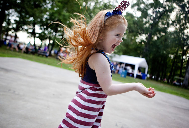 Side view of happy girl dancing at fourth of july event