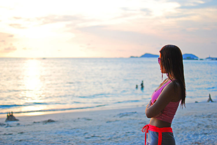 Side View Of Mid Adult Woman Looking At Sea Against Sky During Sunset