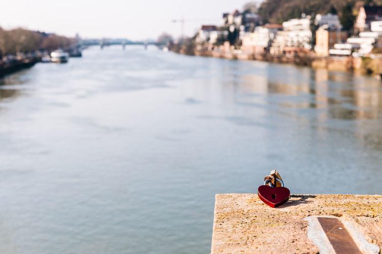 Heart shape padlock at riverbank in city