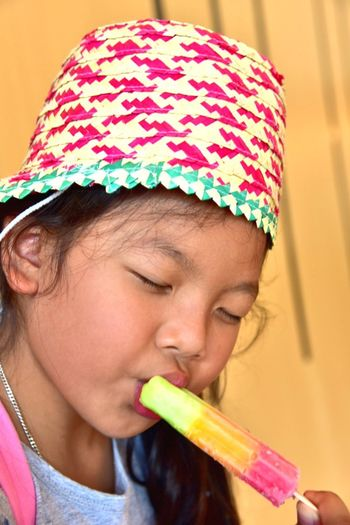 Close-Up Of Cute Girl Eating Ice Lolly