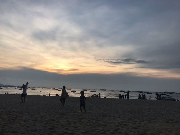 Sky Water Sea Beach Land Sunset Group Of People Crowd Sand Large Group Of People Nature Scenics - Nature Horizon Over Water Horizon Group Holiday Beauty In Nature Cloud - Sky Real People Outdoors