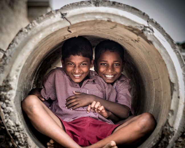 """ENLIGHTENED SMILES"" I Photographed this two kids hidden inside the tunnel pipe at the backyard of the school ,As they were playing hide and seek .The tunnel pipe was enlightened by there smiles."
