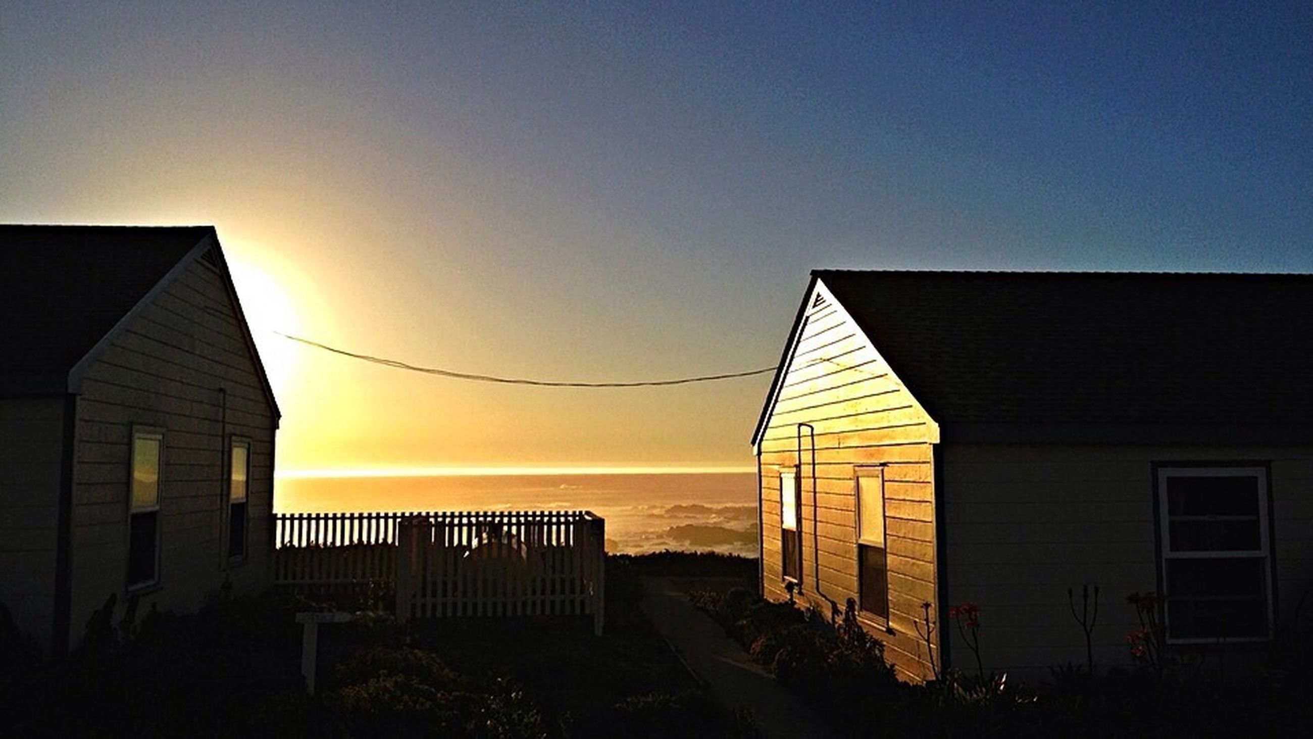 architecture, built structure, building exterior, clear sky, copy space, sunset, house, sky, blue, residential structure, beach, outdoors, building, horizon over water, no people, window, sunlight, sea, residential building, yellow