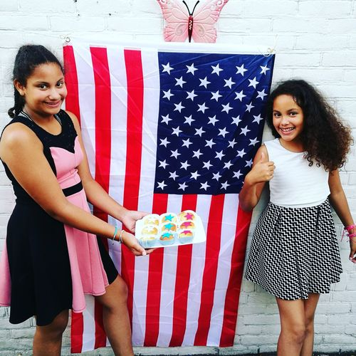 Portrait of siblings holding muffins while standing by american flag smiling young woman