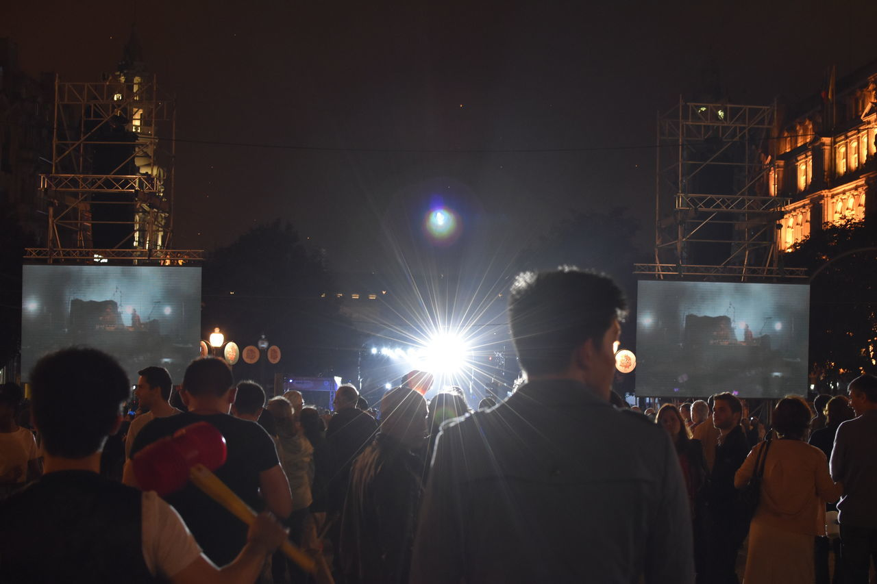 Crowd On Illuminated Street During Event At Night