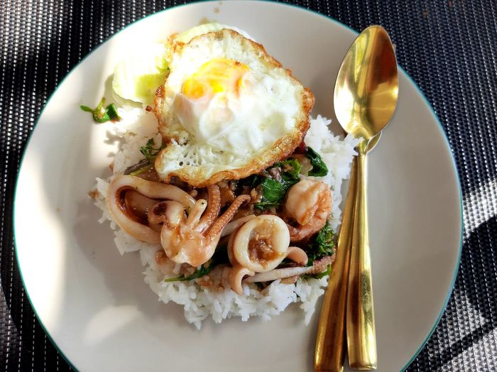 Rice topped with stir-fried seafood and basil fried egg