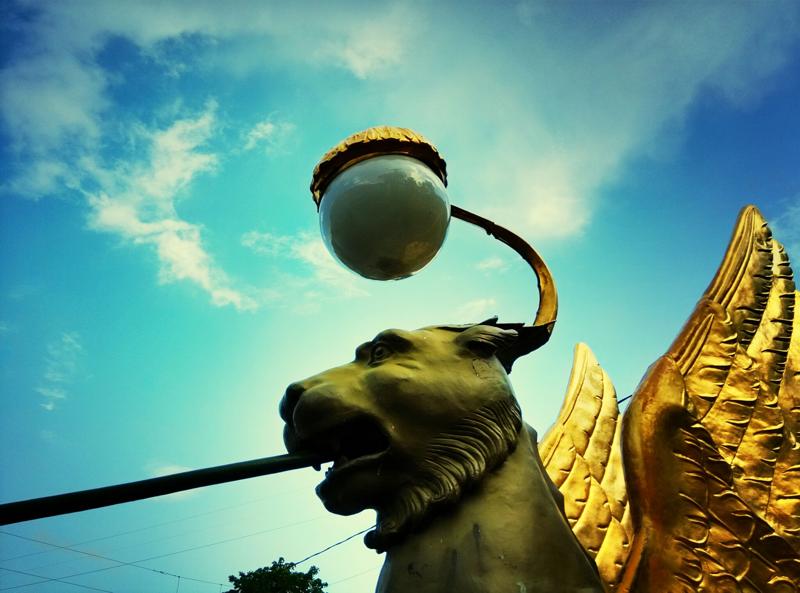 low angle view, sky, sculpture, statue, cloud - sky, art, art and craft, built structure, cloud, lighting equipment, human representation, architecture, animal representation, creativity, street light, outdoors, no people, building exterior, day