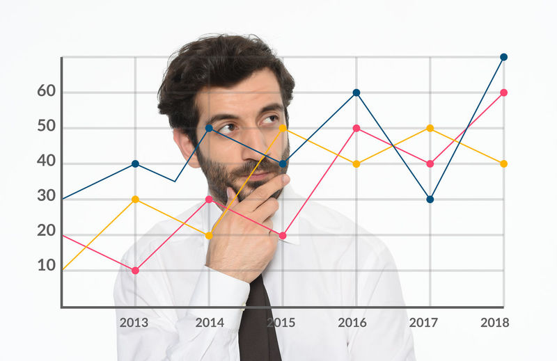 Thoughtful Businessman Looking At Chart In Office