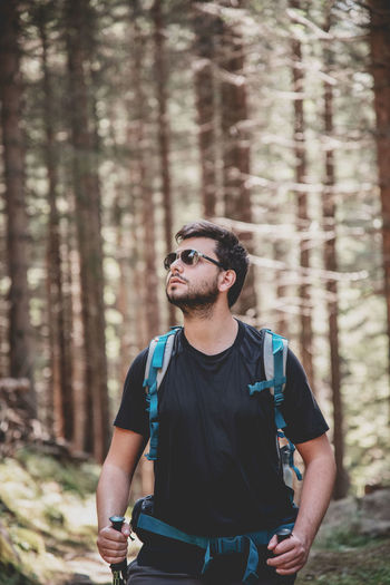 Young man looking away standing in forest