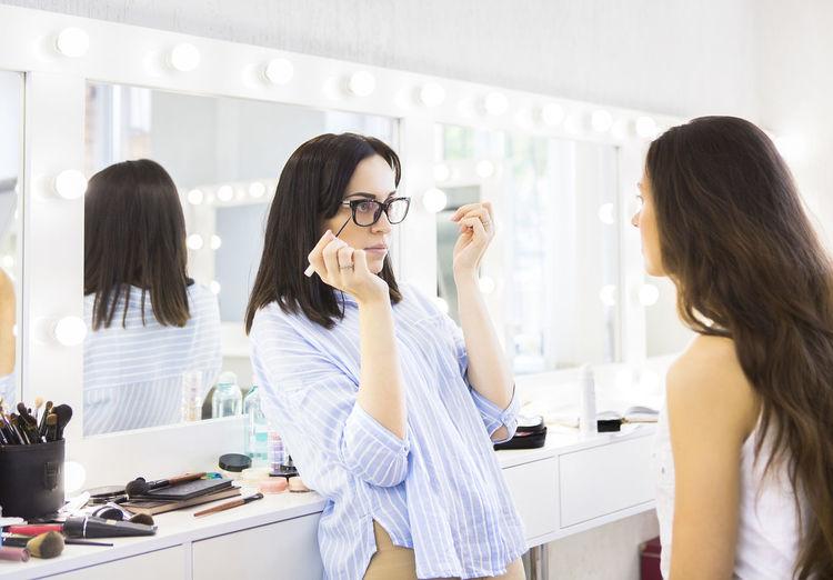 Beautician applying make-up on woman