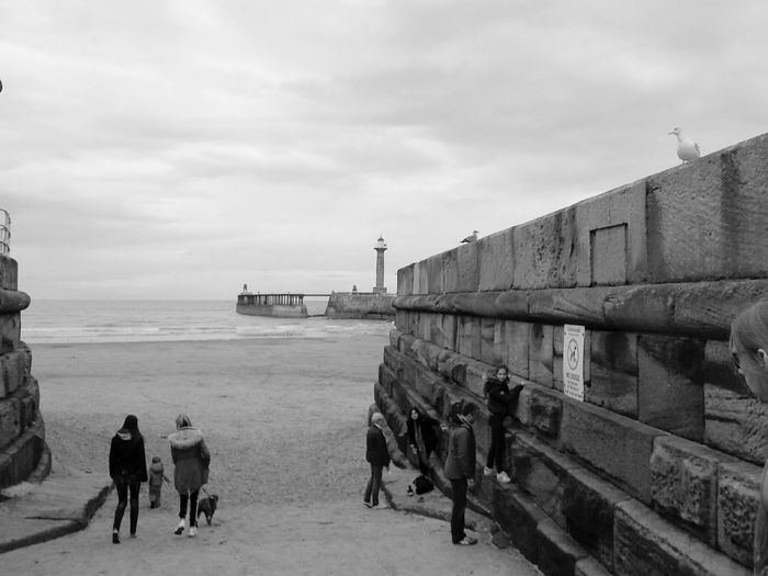 Sea Water Horizon Over Water Architecture Built Structure Lighthouse People Beach Sky Leisure Activity Person Tourists Yorkshire Whitby Building Exterior Shore Vacations Cloud - Sky Outdoors Tranquil Scene Mammal Day Monochrome Photography Black & White Black And White