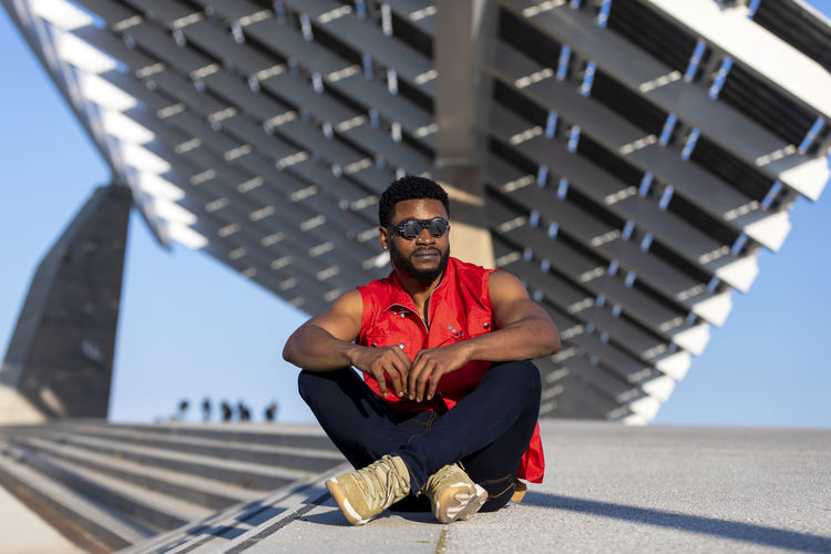 Front view of young black man wearing sunglasses sitting on staircase in a sunny day while looking away Front View One Person Architecture Built Structure Full Length Day Sitting Glasses Lifestyles Looking At Camera Focus On Foreground Real People Sunlight Casual Clothing Nature Building Exterior Portrait Young Men Outdoors African American Sunglasses Looking At Camera Sleeveless  Sitting Staircase Stairs Sunlight Daylight Muscular Build Wellbeing