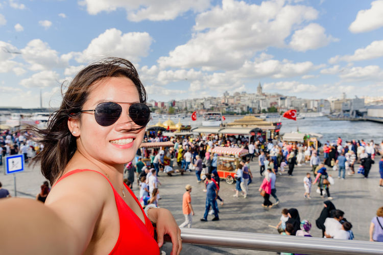 Portrait of woman wearing sunglasses taking selfie while standing by railing
