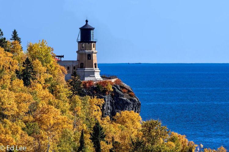 Lighthouse amidst trees and sea against sky